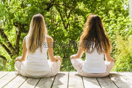 two women practising yoga outdoors