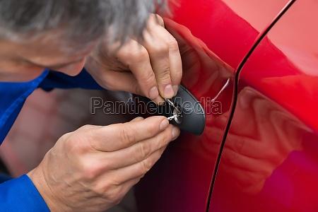 hand holding lockpicker zu oeffnen autotuer