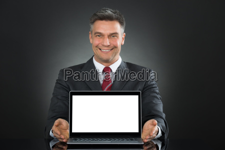 businessman showing laptop with blank screen
