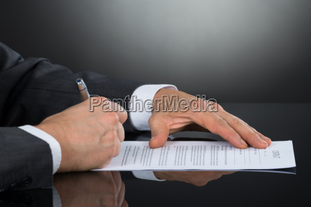 close up of businessperson signing contract