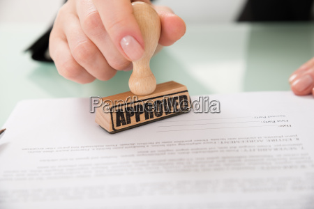 businesswoman hand stamping approved on contract