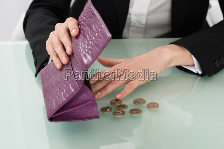 businesswoman holding empty purse with euro