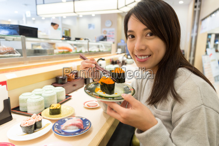 woman enjoy sushi at japanese restaurant