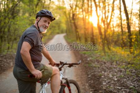 aelterer mann auf seinem mountainbike draussen