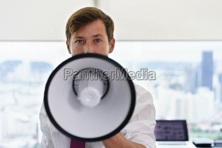 portrait confident business man with megaphone