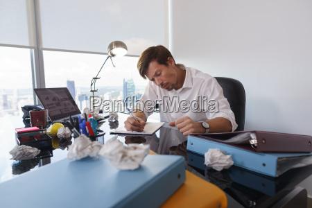 trauriger geschaeftsmann versucht papierbrief zu schreiben