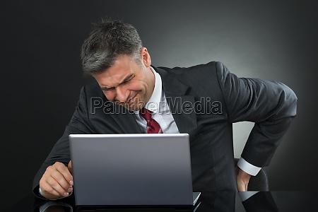 von rueckenschmerzen geschaeftsmann waehrend der arbeit