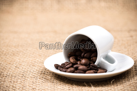 coffeecup with coffeebeans on gunny textile