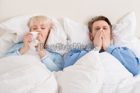 couple blowing their nose while lying