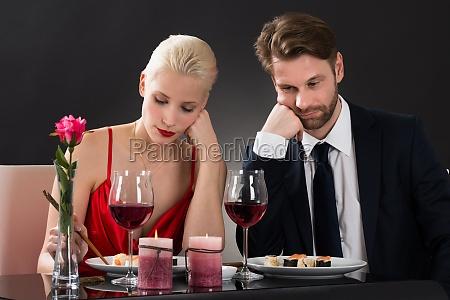 sad couple having dinner at a