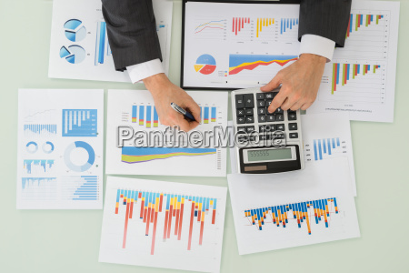 businessman working on calculator for analyzing