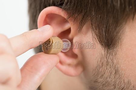 man wearing hearing aid in ear