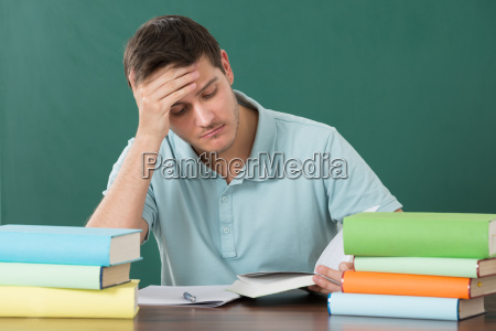 man with books at desk