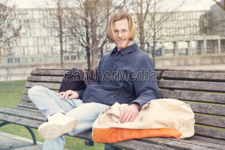 young man with his bags sitting