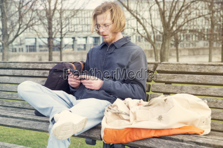 young man sitting on bench and