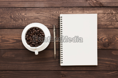 coffee beans in cup and book