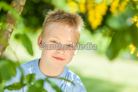 cute blond boy near tree