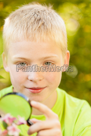smiling boy holding magnifying glass