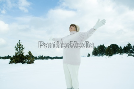 aeltere frau auf schnee stehendie arme