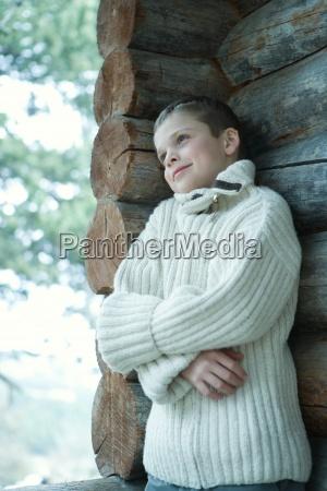 boy tragen wollpulloverdie arme verschraenktlehnte sich