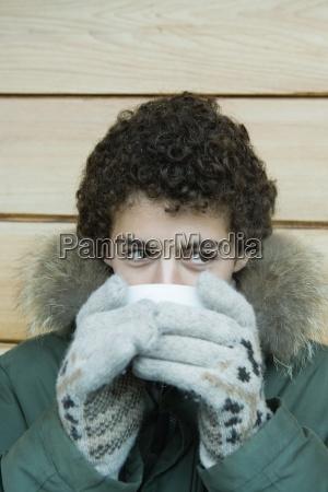 jugendlich junge in der winterkleidung trinken