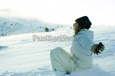 teen maedchen sitzen auf schneedie augen