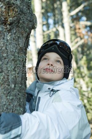 boy hugging tree