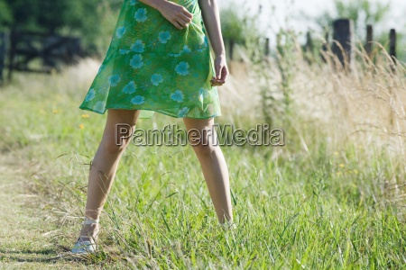 young woman standing in rural field