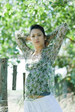 young woman standing in rural setting