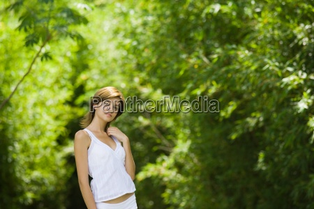 young woman standing in woods with