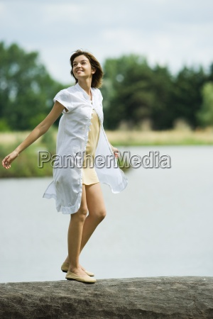 young woman walking across log with