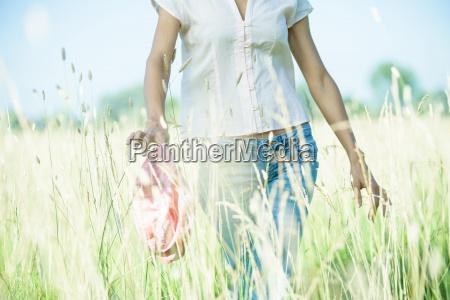 woman walking through field holding hat
