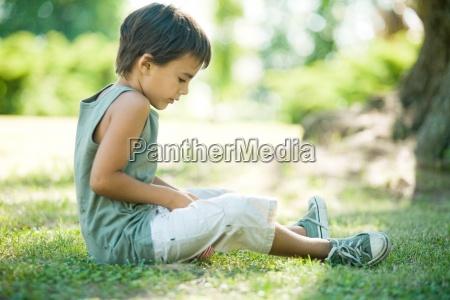 little boy outdoors sitting on grass