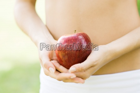 woman holding apple in front of