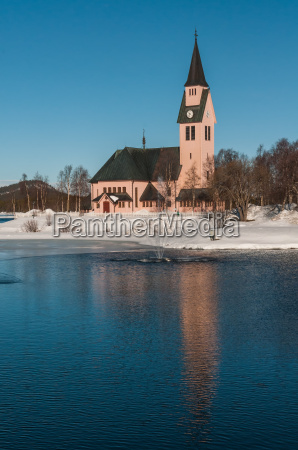 kirche mit holzschinteln vor springbrunnen in