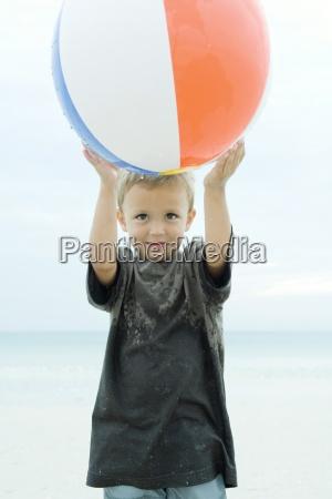 little boy holding up beach ball