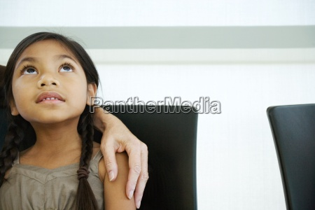 little girl with womans hand on