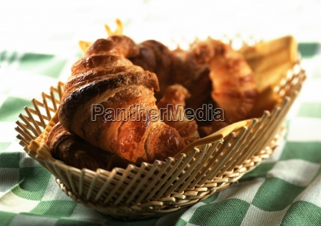 croissants in basket on green checked