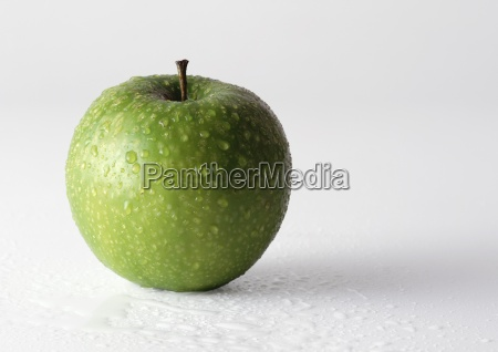 green apple covered with drops of