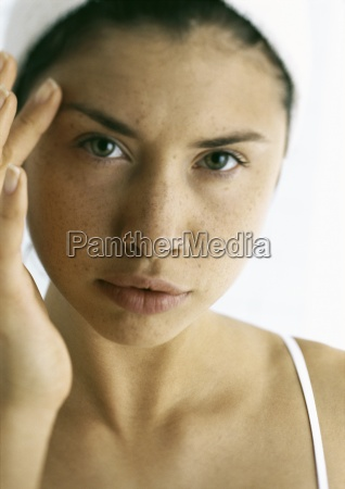 young woman touching face with finger