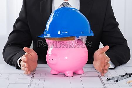 architect hands protecting piggybank wearing construction