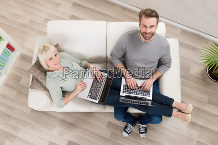 couple relaxing on sofa using laptop