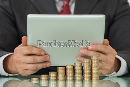 businessman using tablet with stacked coins