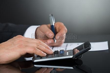 close up of businessman using calculator