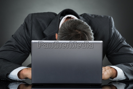 businessman leaning on laptop at desk
