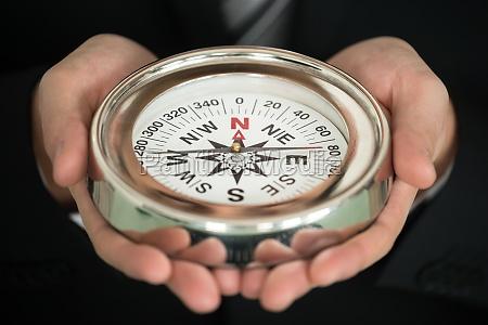 businessman hand holding compass