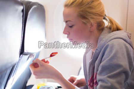 woman eating meal on airplane