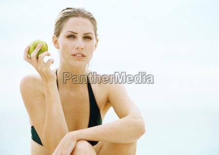 young woman in bikini sitting with