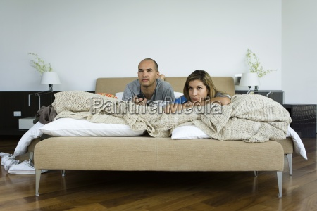 couple lying in bed watching television