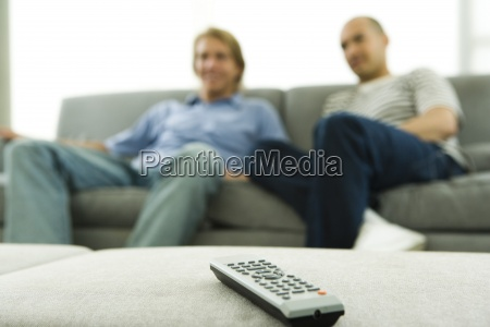 two men sitting on sofa focus